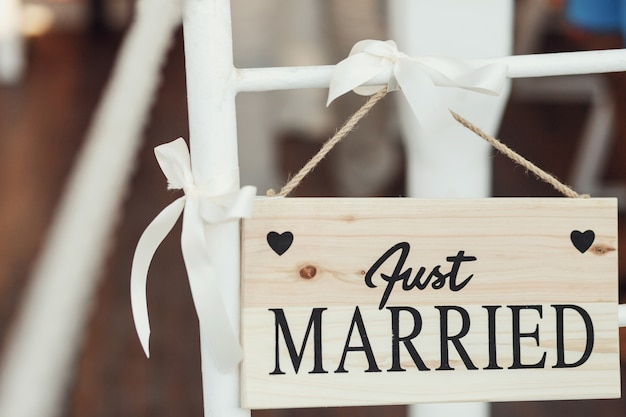 Wooden board with lettering 'just married' hangs on white chair
