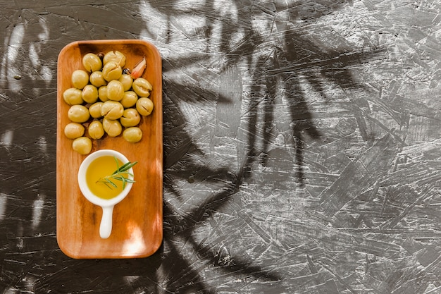 Wooden board with olives and oil