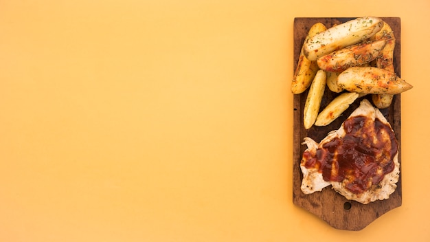 Wooden board with potato wedges and grilled meat
