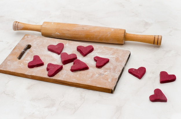 Wooden board with red hearts made of dough. valentine's day