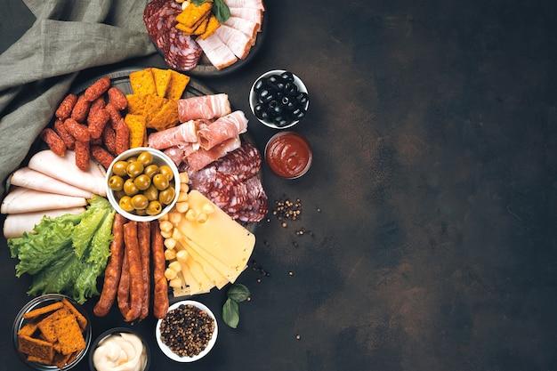 茶色の背景にソーセージとチーズのスライスと木の板