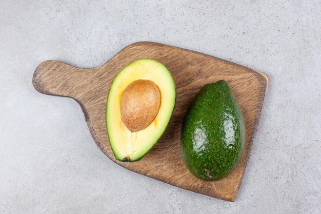 A wooden board with sliced fresh raw avocado