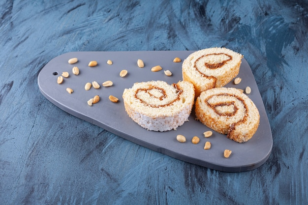 Wooden board with sliced roll cake and peanuts on blue.