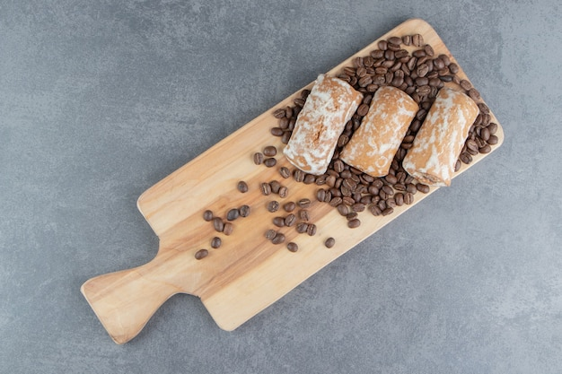 Una tavola di legno con pan di zenzero dolce e chicchi di caffè