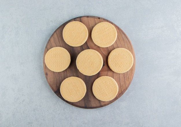 A wooden board with sweet round cookies.