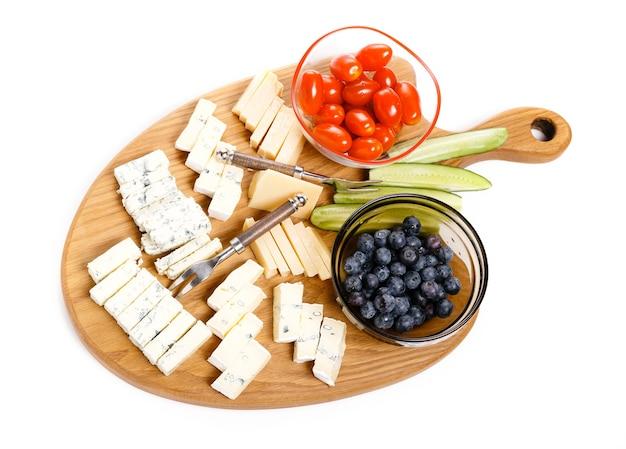Деревянная доска с вкусным сыром и овощами, ягодами, изолированные на белом фоне