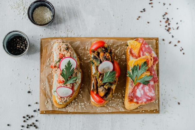 Wooden board with tasty fresh bruschettas on table