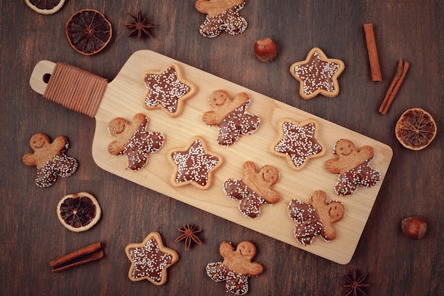 Wooden board with tasty homemade christmas cookies on table