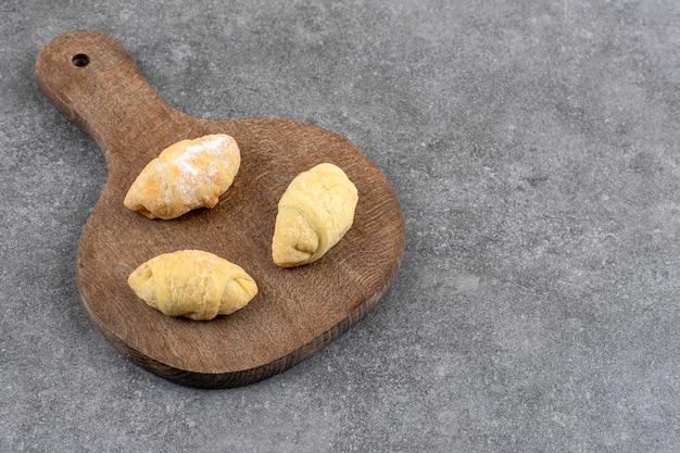 大理石のテーブルに3つの新鮮なクッキーと木の板。