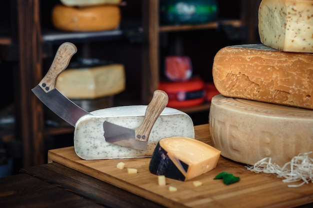 A wooden board with various kinds of tasty cheese on the table with knives and greens