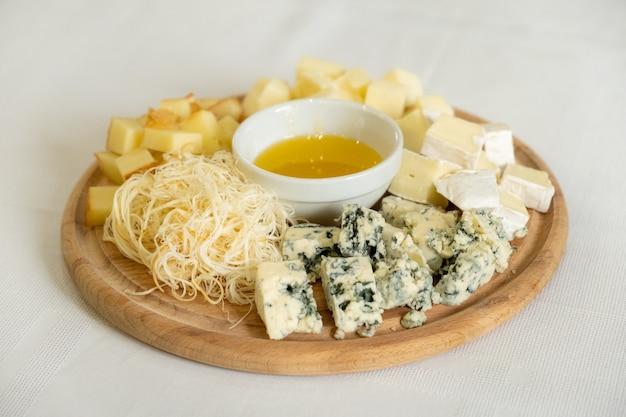 Деревянная доска с различными видами сыров и миской меда, здоровая закуска, выборочный фокус