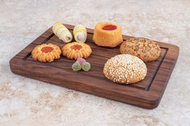 A wooden board with various types of sweet cookies on a stone surface.