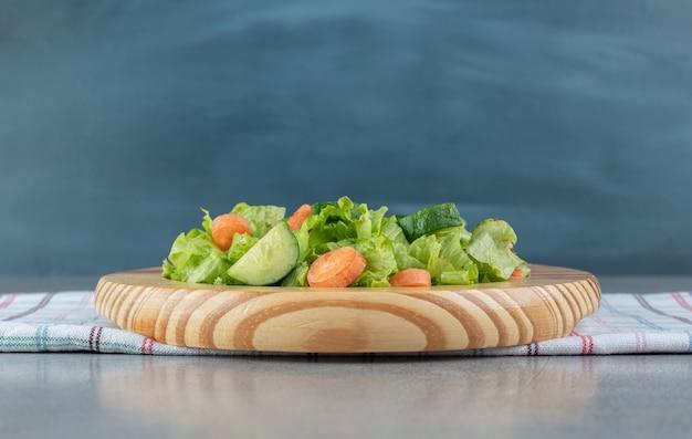 Una tavola di legno con insalata di verdure su una tovaglia. foto di alta qualità