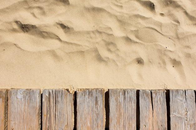 Деревянный дощатый настил, дорожка и легкий мягкий песок. вид сверху.