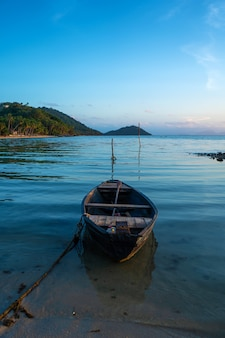 Wooden boat off the coast of a tropical island. evening, sunset in the ocean. tropical landscape. light waves rock the boat