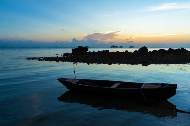 Деревянная лодка у побережья тропического острова. вечер, закат в океане. тропический пейзаж. световые волны качают лодку