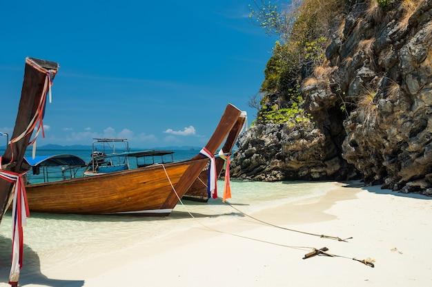 タイのクラビにある白い砂浜と青い空のあるタレウェク島のクリスタルアンダマン海に浮かぶ木製ボート。テキスト用のコピースペースがあるタイ南部の夏の有名な観光旅行先。