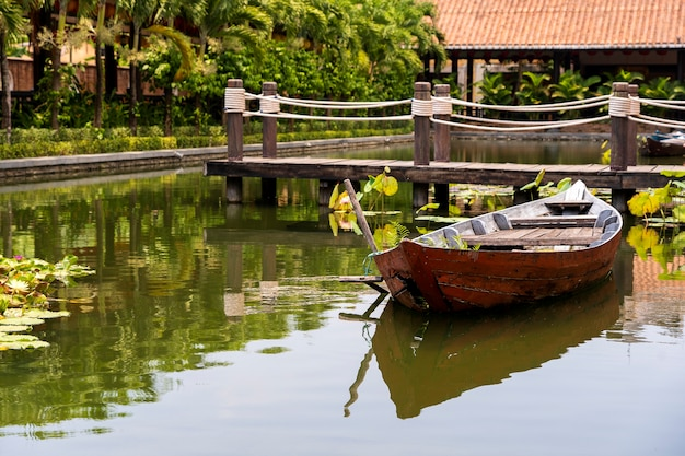 Деревянная лодка на пруду возле пристани в тропическом саду в дананге