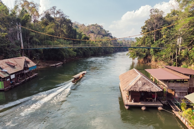 Wooden boat sailing on river kwai with tropical wooden village