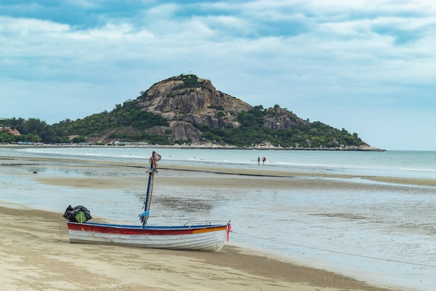Wooden boat on the sand the seaside at suan pradipat in prachuap khiri khan , thailand.