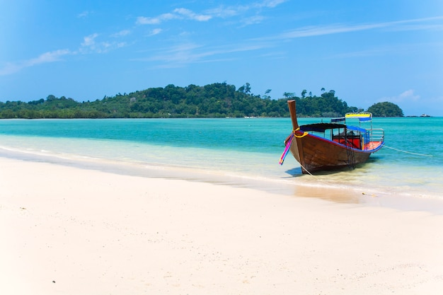 Wooden boat on a white sand beach, blue sea with islands in background, tropical beach in thailand
