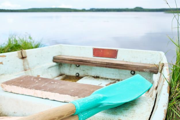 Деревянная лодка с веслом на озере