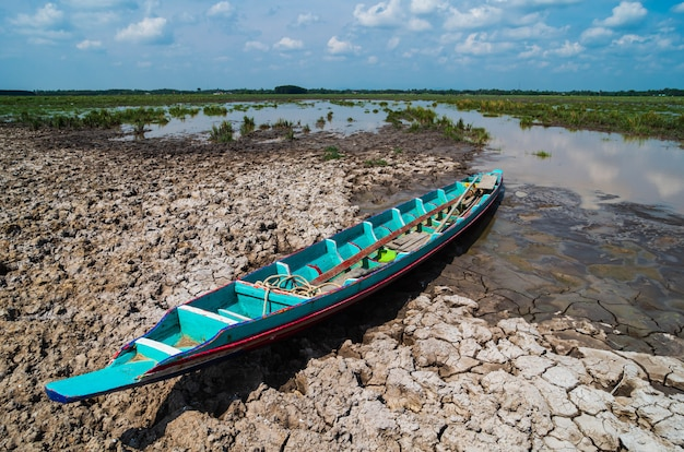 The wooden boat with blue sky and broken soil