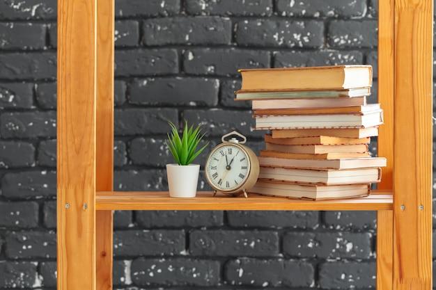 Деревянная книжная полка с книгами и прочим на фоне черной кирпичной стены
