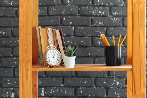 Wooden bookshelf with books and stuff against black brick wall