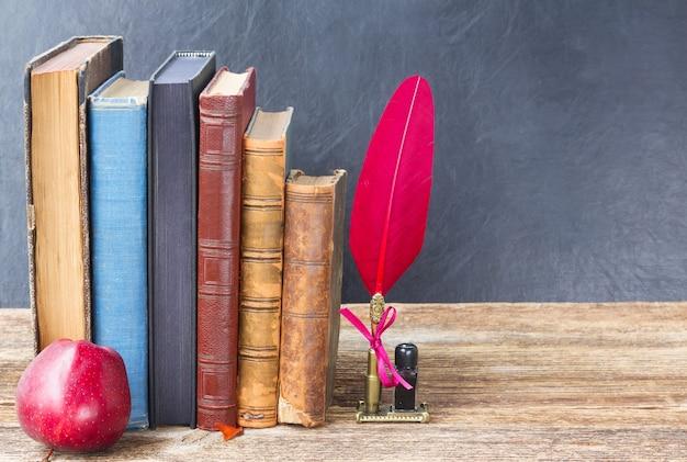 Деревянная книжная полка со старыми книгами, яблоко и красное перо