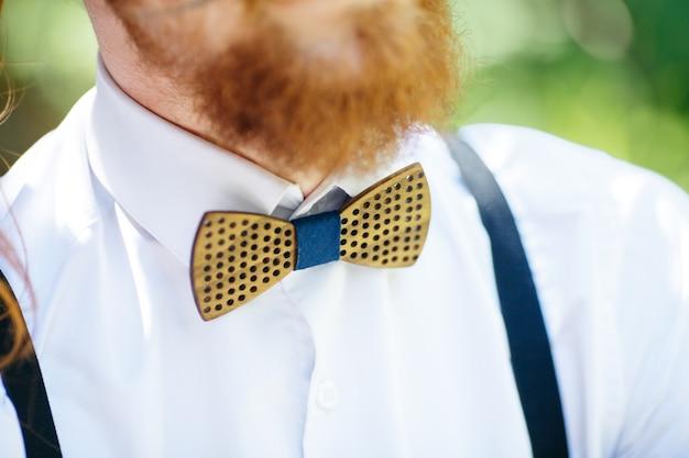 Деревянная галстук-бабочка накрыла белую рубашку под красной бородой