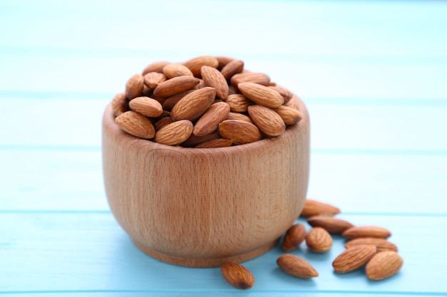 Wooden bowl of almonds on blue background