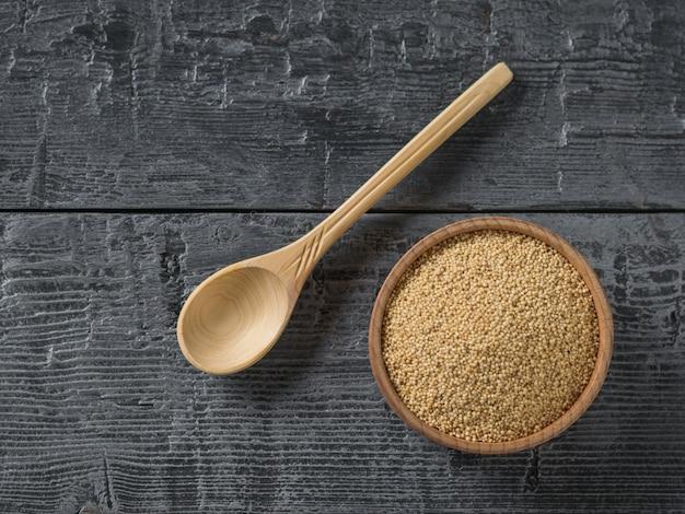 木製のボウルとスプーンで暗い木製のテーブルにアマランスの種子。グルテンフリー食品。