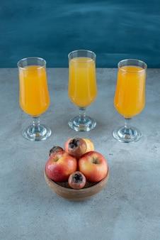 Una ciotola di legno di mele con tazze di vetro di succo d'arancia.