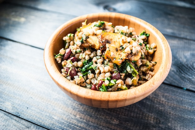 Wooden bowl of boiled buckwheat with fried champignon, spinach and red beans