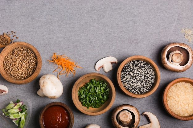 Wooden bowl of chives; coriander seeds; sauce; mushroom; rice grains and grated carrot on grey linen tablecloth