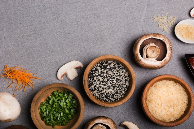 Wooden bowl of chives; sesame seeds; rice grains; mushroom and grated carrot on grey linen cloth