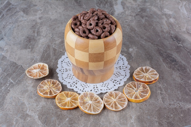 A wooden bowl of chocolate cereal rings with sliced dried orange fruit .