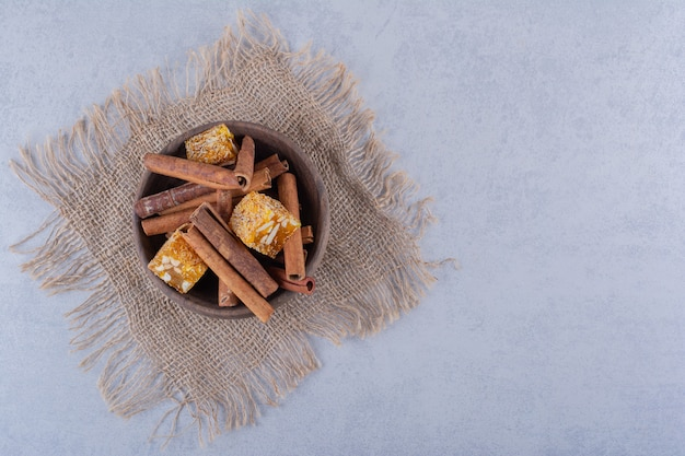 Wooden bowl of cinnamon sticks and nut candies on stone table.