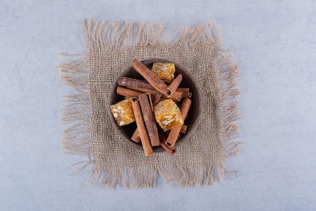 Ciotola di legno di bastoncini di cannella e caramelle alle noci sul tavolo di pietra.