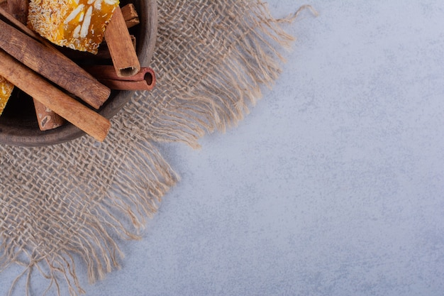 Ciotola di legno di bastoncini di cannella e caramelle alle noci su pietra.