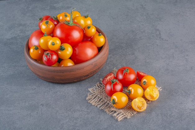 Wooden bowl of colorful organic tomatoes on stone background.