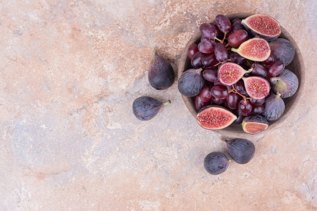 A wooden bowl of cornel berries and purple figs.
