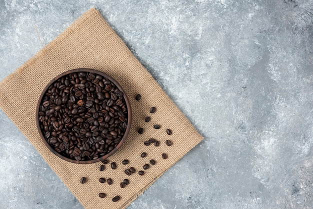 Wooden bowl of dark roasted coffee beans and burlap on marble surface.
