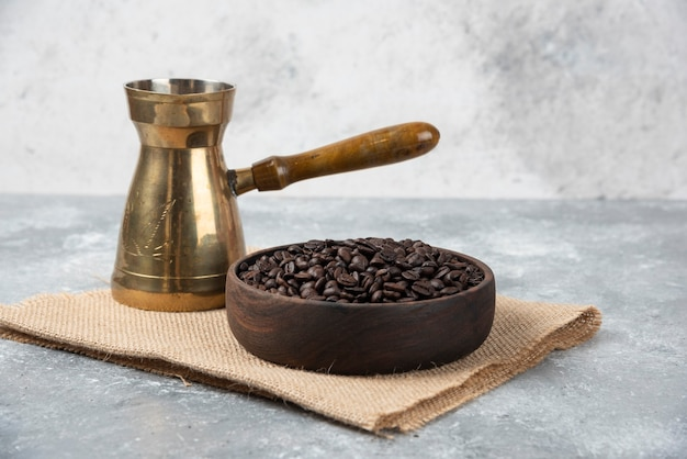 Wooden bowl of dark roasted coffee beans and coffee maker on marble surface.