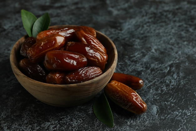 Wooden bowl of dates on black smokey surface