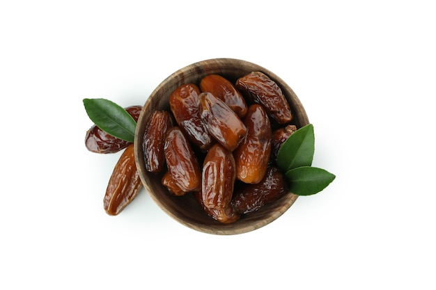 Wooden bowl of dates isolated on white surface
