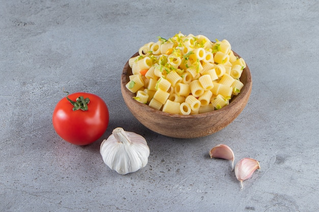 Wooden bowl of delicious boiled pasta on stone surface.