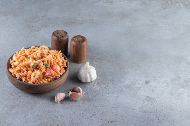 Wooden bowl of delicious fusilli pasta on stone background.