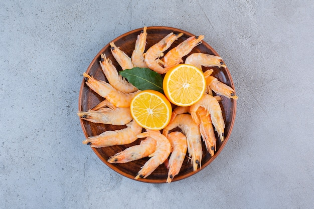 A wooden bowl of delicious shrimps with sliced lemon on a stone background .